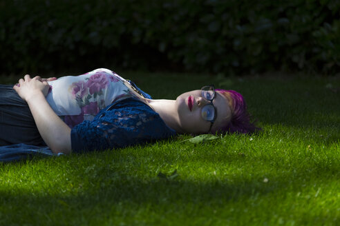 Portrait of relaxed young woman with dyed hair lying on a meadow - BOYF000474
