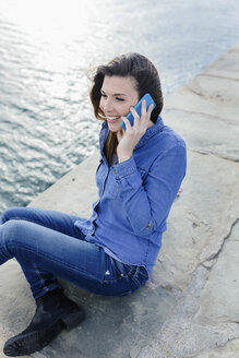 Smiling young woman sitting on dock talking on cell phone - BOYF000480