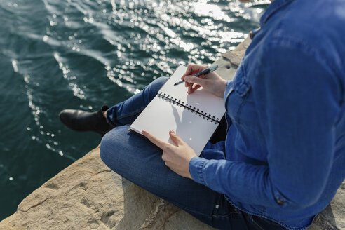 Young woman sitting on dock writing in notebook - BOYF000492