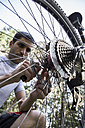 Man examining and adjusting the wheel of a mountainbike - ABZF000890