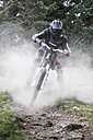 Mountainbiker riding downhill with a dust cloud - ABZF000896