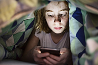 Girl lying under blanket in bed looking at her smartphone - JATF000873