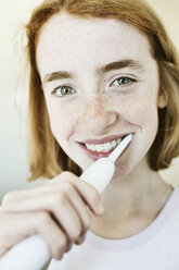 Portrait of smiling girl brushing teeth with electric toothbrush - JATF000876