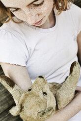 Girl holding teddy bear in her arms - JATF000879