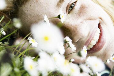 Smiling girl lying on field of flower, close-up - JATF000882