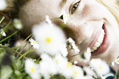 Smiling girl lying on field of flower, close-up - JATF000882