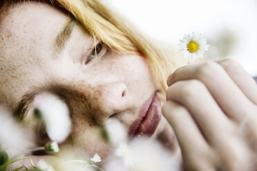 Girl holding daisy in her hand, close-up - JATF000885