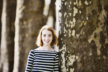 Smiling girl leaning ageinst tree trunk - JATF000888