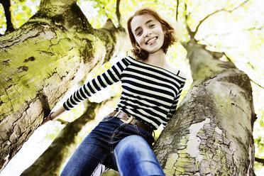 Smiling girl climbing on a tree - JATF000891