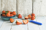 Bowl of strawberries and kitchen knife on wood - ASF005955