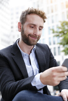 Smiling young businessman looking at cell phone outdoors - FKF002024