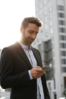 Smiling young businessman looking at cell phone outdoors - FKF002027