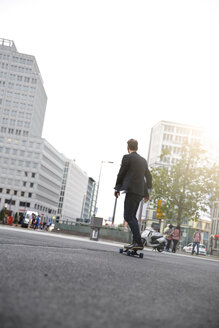 Young businessman on skateboard in the city - FKF002039