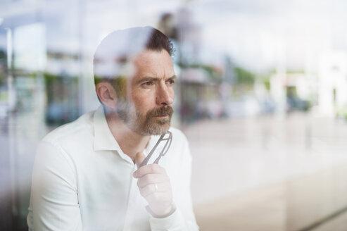Portrait of serious businessman looking through window - DIGF000910
