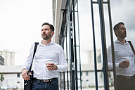 Serious businessman with coffee to go in front of glass facade - DIGF000913