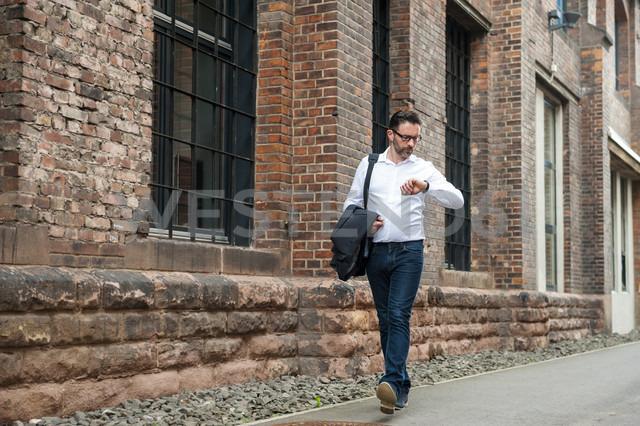 Walking businessman checking the time - DIGF000919