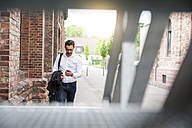 Walking businessman looking at cell phone - DIGF000922