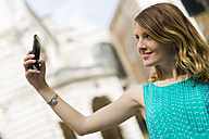 Smiling young woman taking selfie with smartphone - GIOF001348