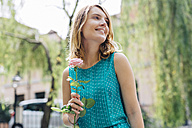 Smiling young woman with rose blossom - GIOF001351