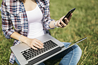 Young woman sitting on a meadow using laptop and smartphone, partial view - GIOF001369