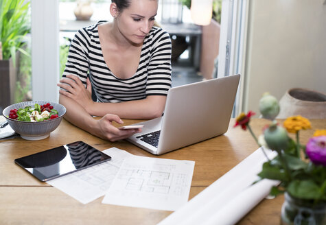 Woman at desk using laptop and cell phone next to construction plan and salad - REAF000113