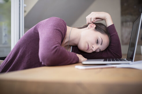 Tired young woman sleeping at desk - REAF000119
