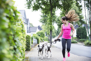 Young woman jogging with two dogs - REAF000143