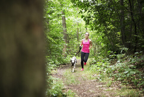 Young woman jogging with dog in forest - REAF000146
