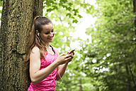 Sportive young woman with smartphone and earbuds - REAF000149