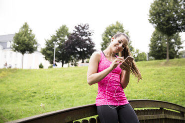 Sportive young woman with smartphone and earbuds - REAF000152