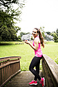 Happy sportive young woman with smartphone and earbuds - REAF000155