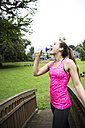 Sportive young woman drinking from bottle - REAF000158