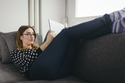 Young woman relaxing on the couch with her tablet - LCUF000034