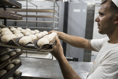 Baker placing a tray of bread dough in a bakery - ABZF000913