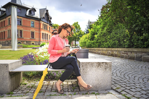 Woman with coffee to go resting on a bench looking at cell phone - VTF000543