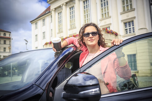 Portrait of woman wearing sunglasses getting on her car - VTF000546
