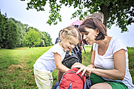 Mother and daughters during hiking, looking into backpack - VTF000549