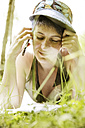 Woman lying on a meadow telephoning with cell phone - JATF000917