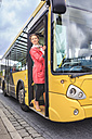 Young woman getting into bus - VTF000556
