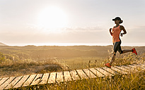 Spain, Aviles, young athlete woman running along a coastal path at sunset - MGOF002121