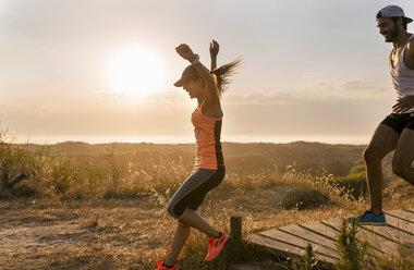 Spain, Aviles, athletes couple running along a coastal path at sunset - MGOF002124
