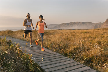 Spain, Aviles, athletes couple running along a coastal path at sunset - MGOF002130
