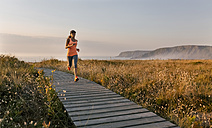 Spain, Aviles, young athlete woman running along a coastal path at sunset - MGOF002133