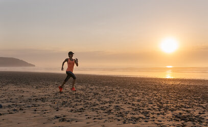 Athlete woman running on the beach at sunset - MGOF002142