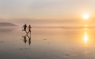 Athletes couple running on the beach at sunset - MGOF002145