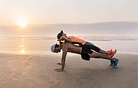 Athletes couple training on the beach at sunset, pushups - MGOF002148