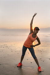 Young athlete woman doing stretching on the beach at sunset - MGOF002154