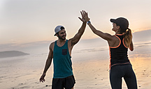 Athletes couple hitting five on the beach at sunset - MGOF002157