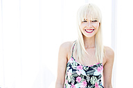 Portrait of smiling blond woman in front of light background - GDF001086