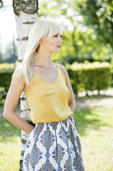 Blond woman leaning against tree trunk - GDF001089